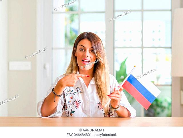Young woman at home holding flag of Russia very happy pointing with hand and finger