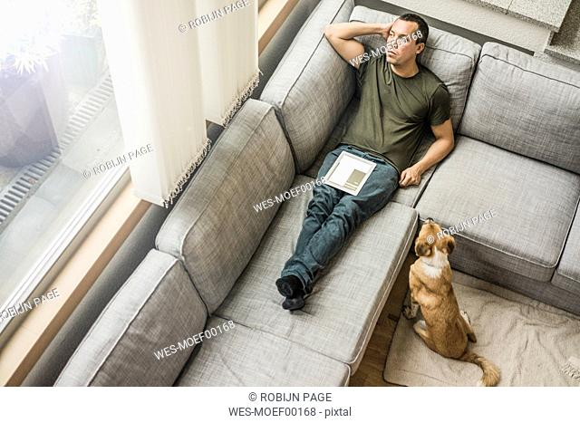 Man at home with tablet on the couch with dog beside him