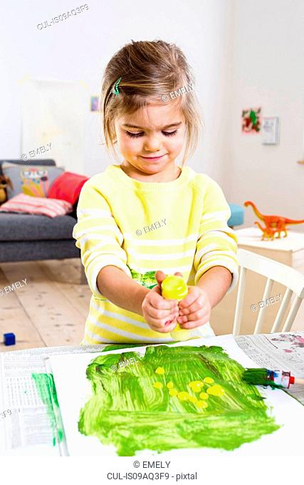 Girl playing with paint at home