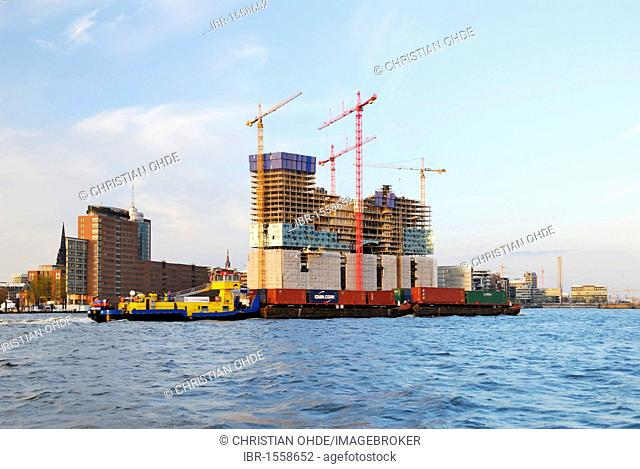 Barge laden with containers on the Elbe river and the Elbphilharmonie philharmonic hall under construction in the Hafencity district, Hamburg, Germany, Europe