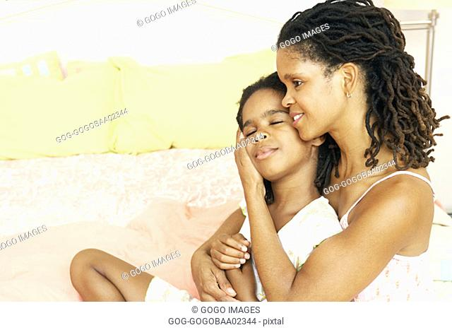 African mother hugging her daughter