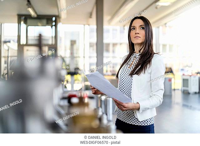 Businesswoman holding plan in modern factory