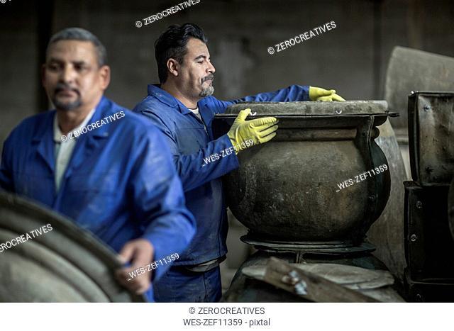 Two men working in industrial pot factory