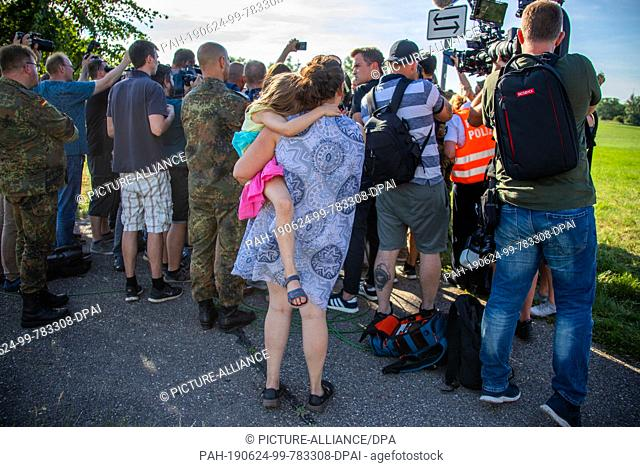 24 June 2019, Mecklenburg-Western Pomerania, Jabel: A resident of Jabel with a child in her arms follows the press release of the Federal Minister of Defence...