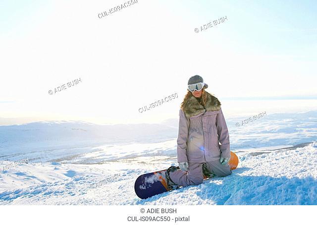 Snowboarder kneeling in snow, Are, Sweden