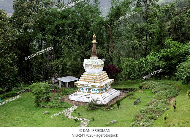 A large Buddhist chorten decorated with Tibetan text rests in the jungle at the Lingdum Monastery in Sikkim, India. - SIKKIM, INDIA, 06/06/2010