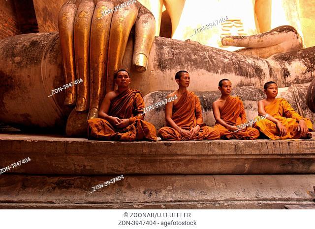 Moenche bestaunen die Buddha Figur im Wat Si Chum Tempel in der Tempelanlage von Alt-Sukhothai in der Provinz Sukhothai im Norden von Thailand in Suedostasien