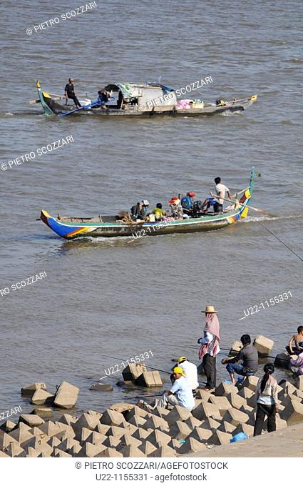 Phnom Penh (Cambodia): men fishing and canoes by the Sisowath Quay, at the confluence of the Tonlé Sap, Mekong, and Bassac rivers