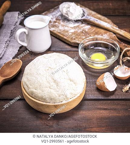 yeast dough in a wooden bowl on a brown table, behind ingredients