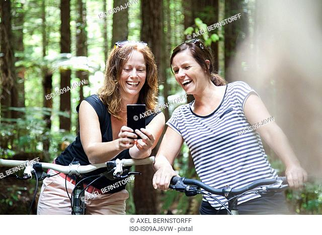 Two women mountain bikers looking at smartphone in forest