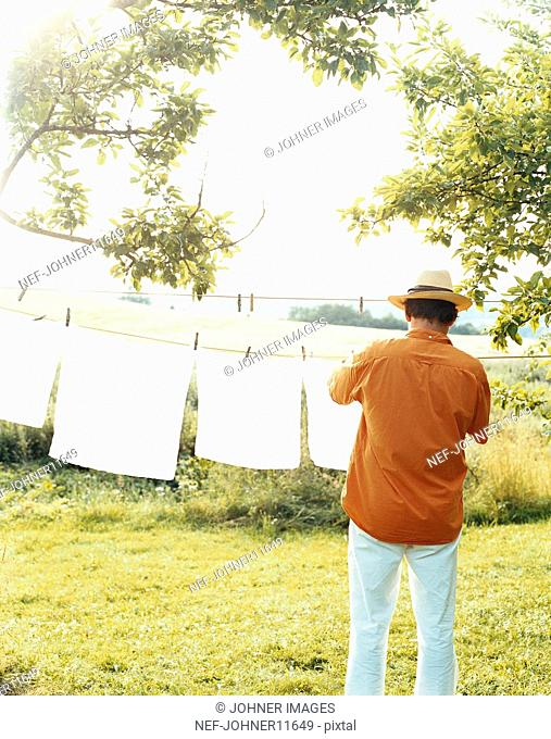 Man hanging laundry on the line outdoors