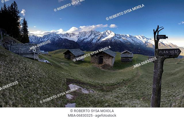 Panorama of huts and valley framed by snowy peaks at dawn Tombal Soglio Bregaglia Valley canton of Graubünden Switzerland Europe
