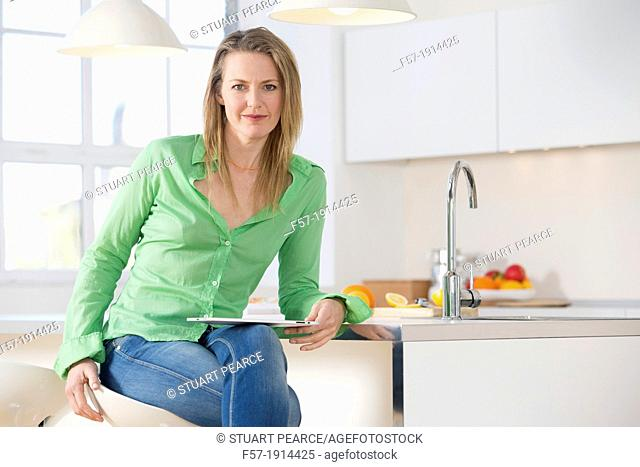 Attractive young woman using her tablet computer in her kitchen