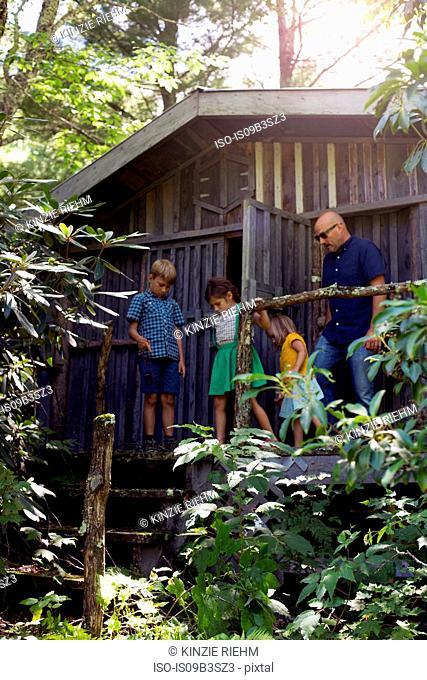 Family standing outside wooden cabin