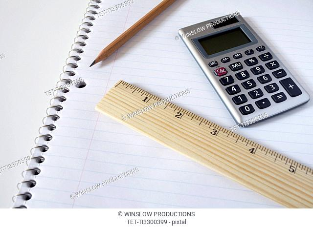 Calculator, ruler and pencil on notebook, studio shot