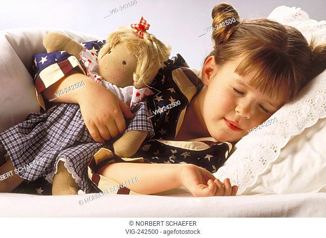 portrait, indoor, 7-year-old girl wearing a blue pyjama with stars lies with her puppet in her arm in bed sleeping  - GERMANY, 26/02/2005