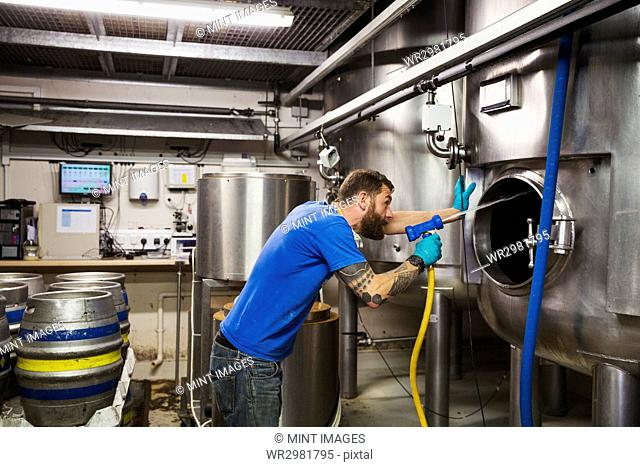Man working in a brewery, cleaning inside of a large stainless steel kettle with a high pressure washer