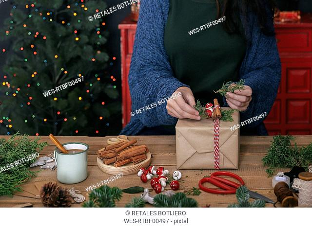 Woman decorating Christmas present, partial view