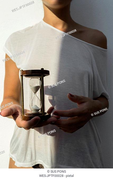 Young woman holding an hourglass at sunset against white wall