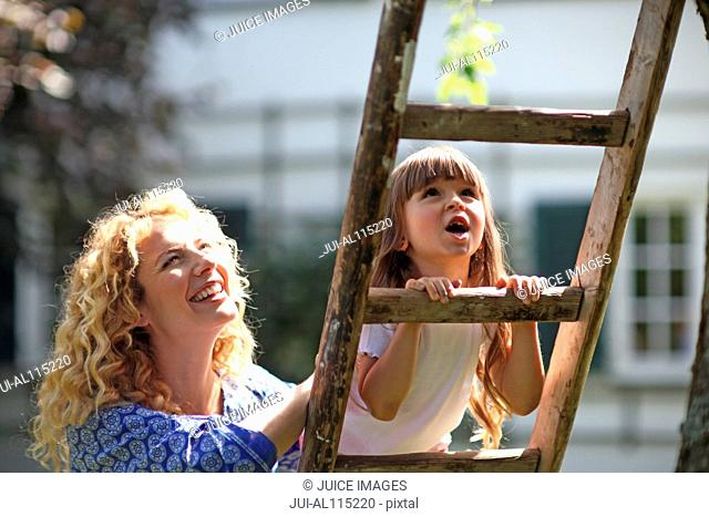 Mother helping daughter to climb ladder