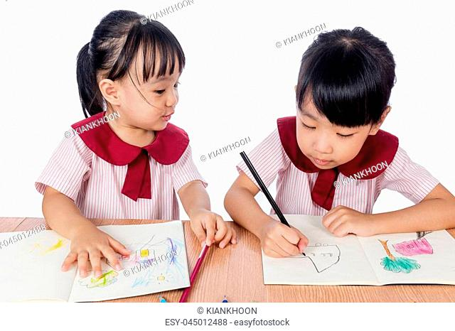 Asian Little Chinese girls drawing with color pencils in isolated white background