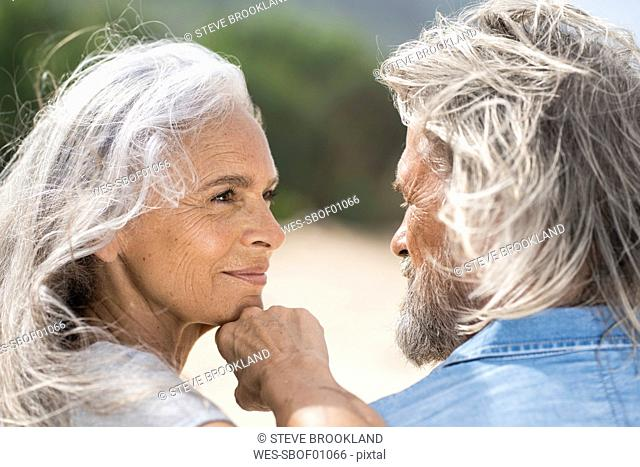 Beautiful senior woman smiling at her husband