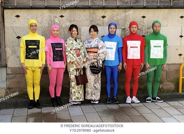 Group of japanese men disguised with colorful costume posing for a photo with women in traditional clothing, Kanazawa, Japan, Asia