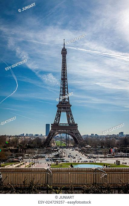 View of the Eiffel Tower in Paris on the Champs de Mars against a blue sky, one of the most visited and iconic landmarks in France with its distinctive wrought...