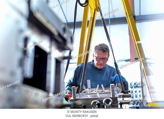 Engineer working on mould for plastic injection in precision engineering factory
