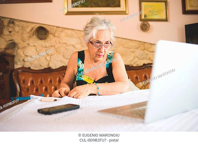 Woman making a quilt, using laptop