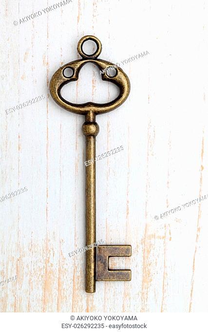 Antique rusty key on wood background