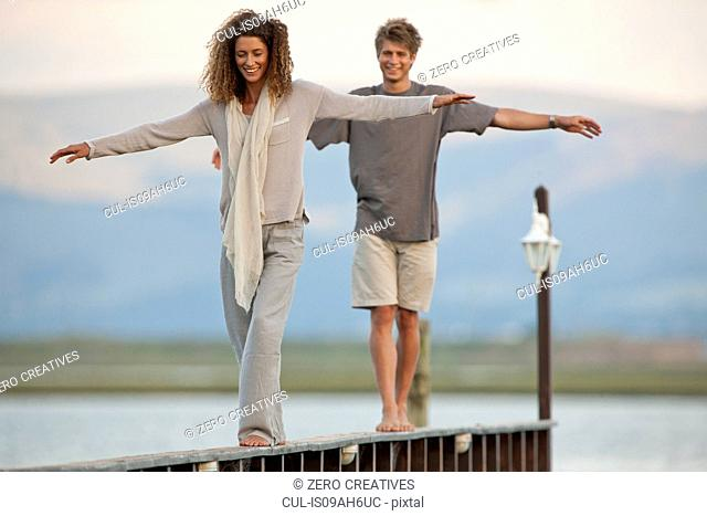 Young couple balancing on jetty