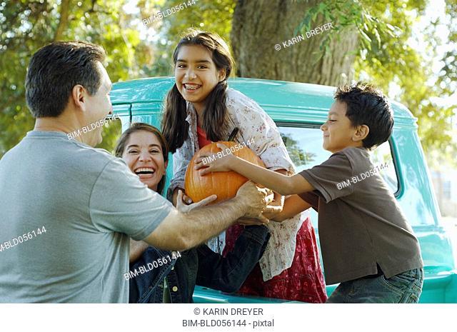 Multi-ethnic family holding pumpkin