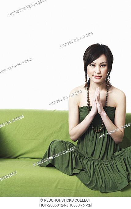 Portrait of a young woman sitting on a couch in a prayer position