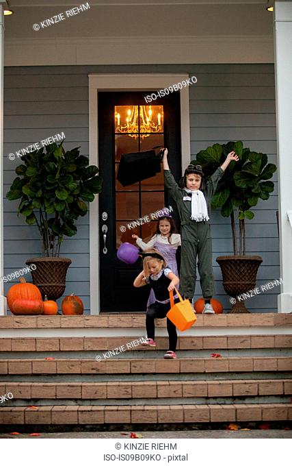 Boy and sisters trick or treating celebrating on porch