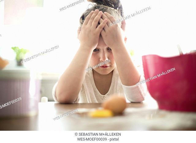 Little girl watching broken egg on kitchen table