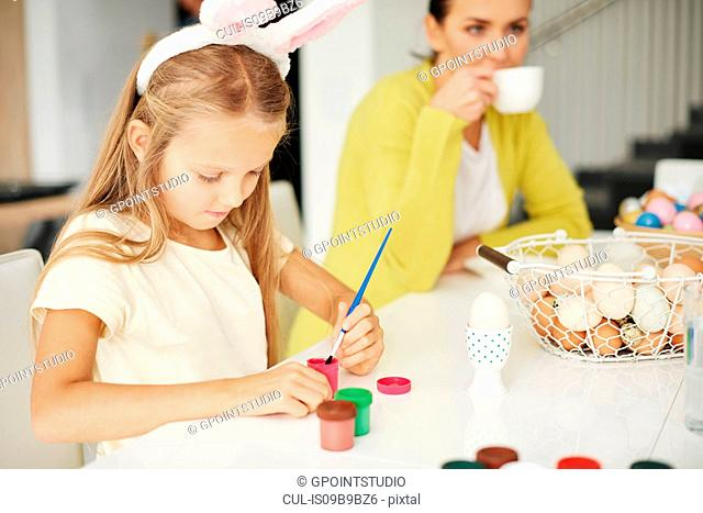 Girl painting hard boiled easter egg at table