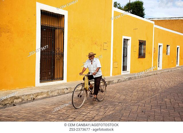 Man riding on a bike in the streets of the town, Izamal, Yucatan, Yucatan Province, Mexico, Central America