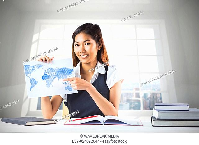 Composite image of smiling businesswoman pointing a sheet of paper