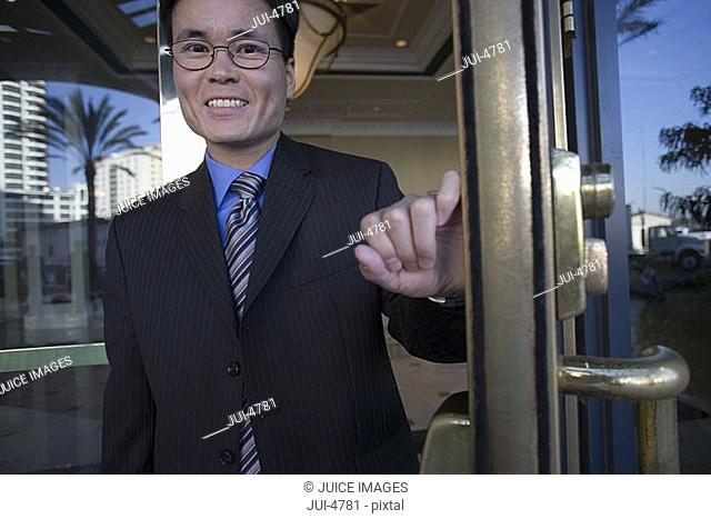 Businessman in spectacles opening door, exiting building lobby, smiling, front view, portrait