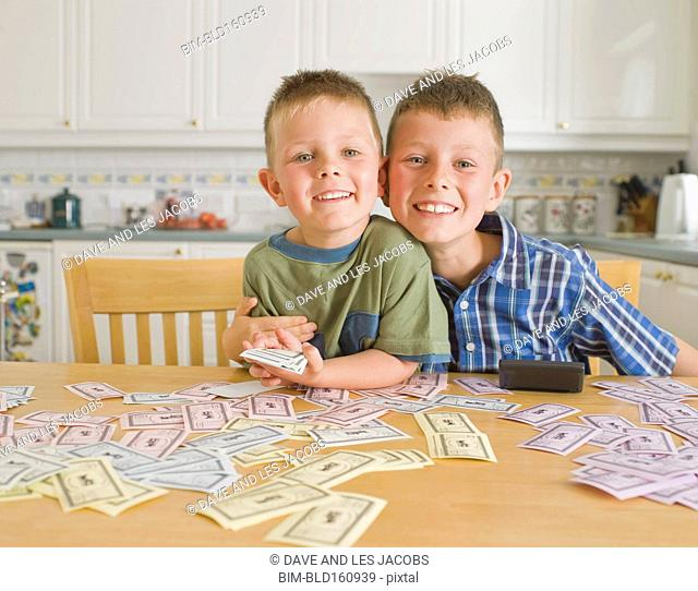 Caucasian brothers counting toy money in kitchen