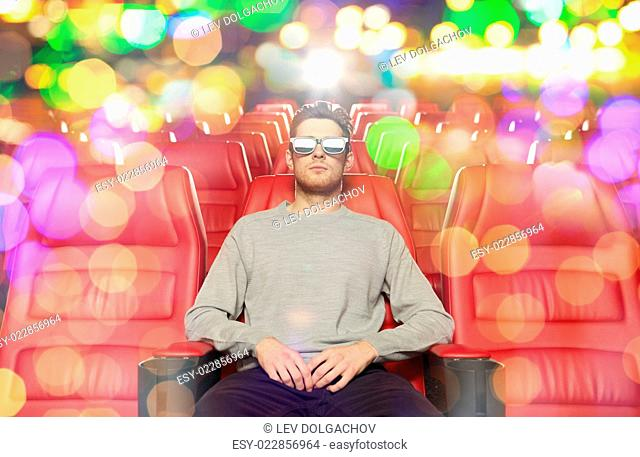 cinema, technology, entertainment and people concept - young man with 3d glasses watching movie alone in empty theater auditorium