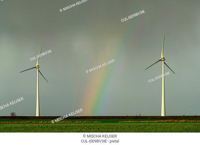 Field landscape with rainbow between two turbines on wind farm in north Netherlands, near waddensea dyke