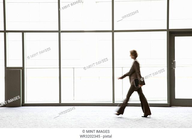 A businesswoman blurred in silhouette while walking past a large convention centre window