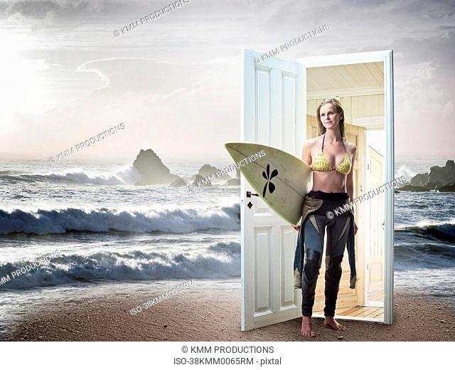 Woman emerging from door on beach