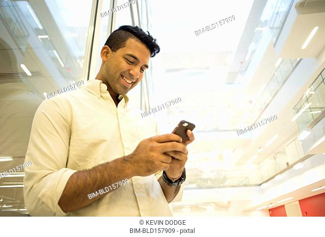 Asian businessman texting on cell phone