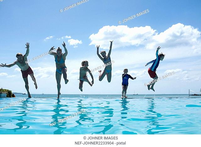 Family jumping into swimming-pool