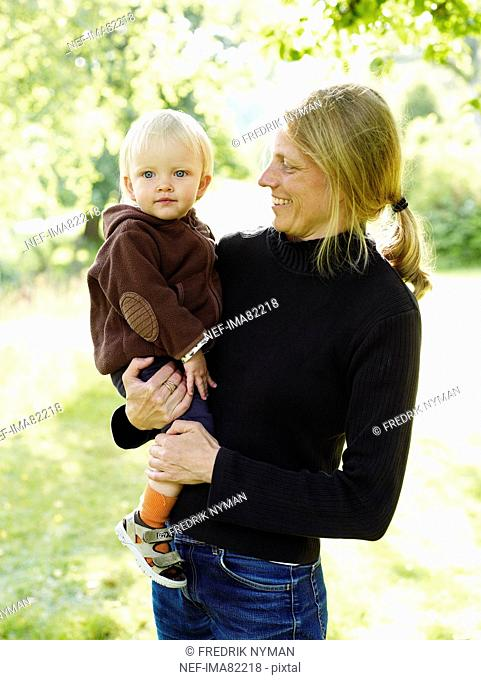 Woman carrying baby, smiling