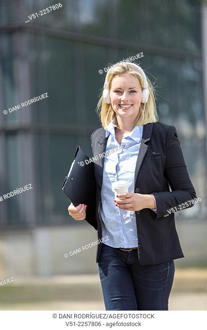 Pretty executive woman walking with coffee and headphones outdoors and smiling at camera