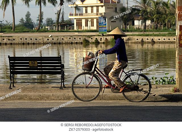 Cyclists woman on the promenade at the Thu Bon River in Hoi An Vietnam. Typical vietnamise woman with hat